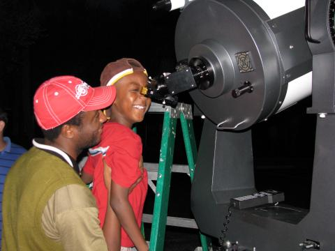 Father and son take a peek through the telescope